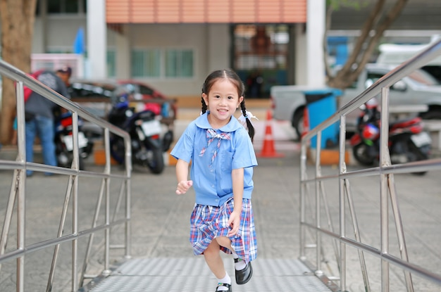 Lächelndes kleines asiatisches kindermädchen in der schuluniform, die herauf metalltreppe läuft
