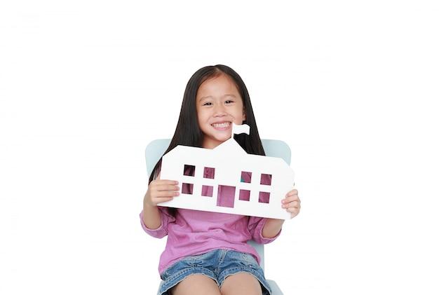 Lächelndes kleines asiatisches kindermädchen, welches die modellpapierschule sitzt auf dem kinderstuhl lokalisiert hält. bildung und zurück zum schulkonzept.