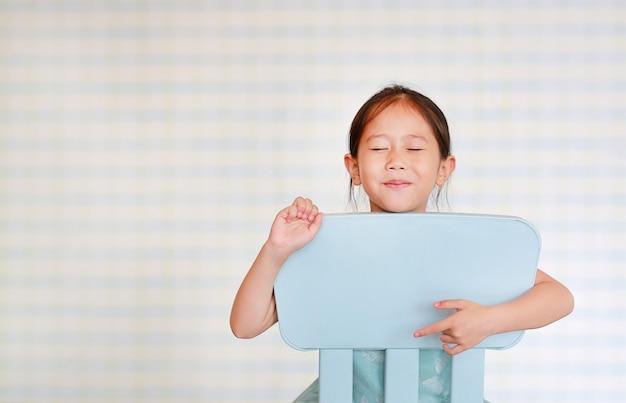 Lächelndes kleines asiatisches kindervorschulmädchen in einem kindergartenraum wirft auf plastikbabystuhl auf