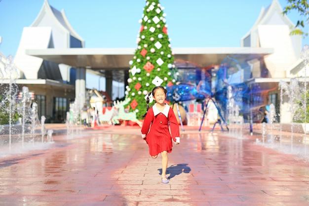 Lächelndes kleines asiatisches mädchen im roten kleid, das um den großen weihnachtsbaum verziert, der für das glückliche neue jahr und das frohe weihnachtsfest dekorativ ist.