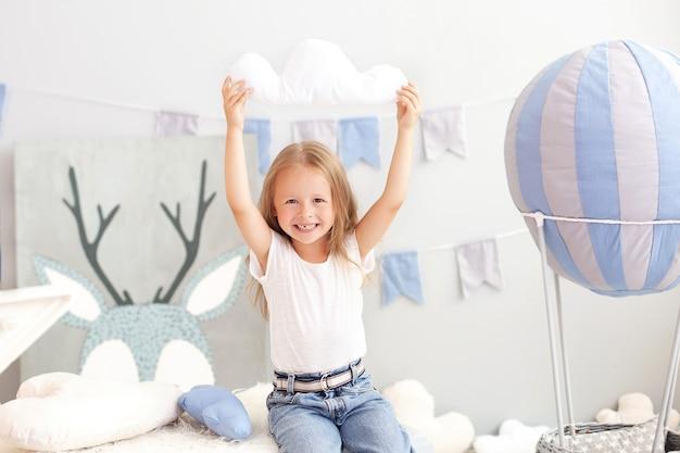 Lächelndes kleines blondes mädchen, das ein wolkenkissen auf der wand eines dekorativen ballons hält. das kind spielt im kinderzimmer mit spielzeug. das konzept der kindheit, reisen. kleinkind im kindergarten
