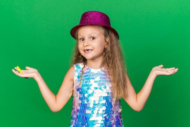 Lächelndes kleines blondes mädchen mit lila partyhut, der partypfeife hält und hand offen hält auf grüner wand mit kopienraum