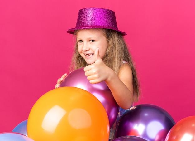 Lächelndes kleines blondes mädchen mit lila partyhut stehend mit heliumballons, die lokalisiert auf rosa wand mit kopienraum daumen hoch