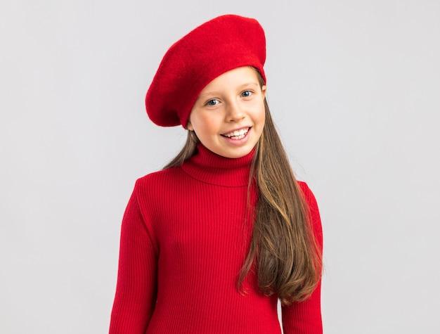 Lächelndes kleines blondes mädchen mit rotem barett, das auf der vorderseite isoliert auf weißer wand mit kopienraum schaut