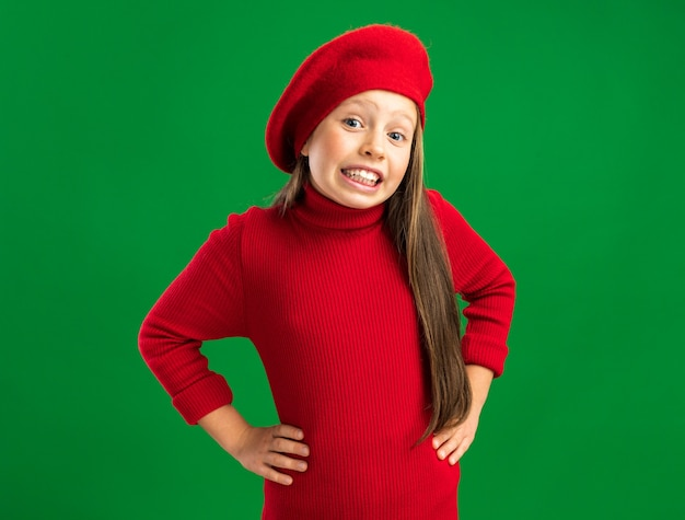 Lächelndes kleines blondes mädchen mit rotem barett, das nach vorne schaut und die hände auf dem bauch hält, isoliert auf grüner wand mit kopierraum