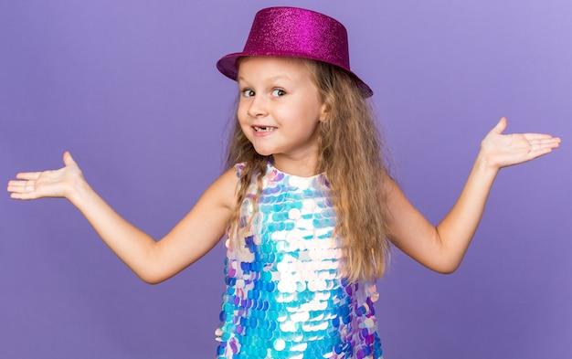 Lächelndes kleines blondes mädchen mit violettem partyhut, das die hände offen hält, isoliert auf lila wand mit kopierraum