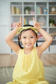 Lächelndes kleines chinesisches mädchen, das zu hause sitzt und kuhhörner gestikulieren lässt