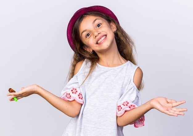 Lächelndes kleines kaukasisches mädchen mit lila partyhut, das partypfeife hält und die hand isoliert auf weißer wand mit kopienraum offen hält?
