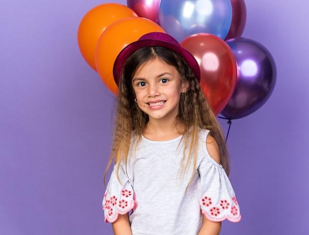 Lächelndes kleines kaukasisches mädchen mit violettem partyhut, das mit heliumballons steht, lokalisiert auf lila wand mit kopienraum