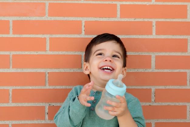 Lächelndes kleines kind, das eine flasche nimmt