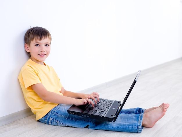 Lächelndes kleines kind mit laptop, der im leeren raum - drinnen sitzt