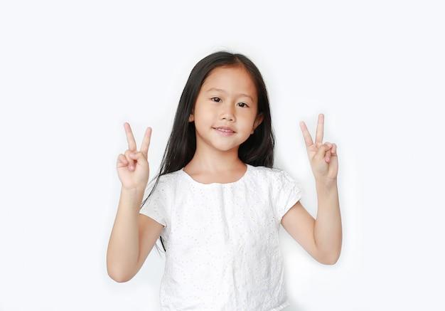 Lächelndes kleines kindermädchen, das zwei finger geste als zeichen als kampf isoliert zeigt