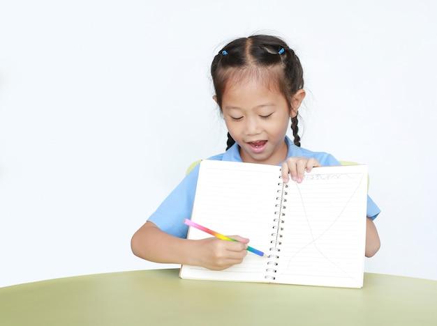 Lächelndes kleines kindermädchen in der schuluniform zeigen schreiben auf leerem notizbuch, das am schreibtisch isoliert sitzt.