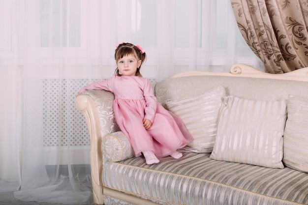 Lächelndes kleines mädchen auf sofa im rosa kleid zu hause. kindheitskonzept
