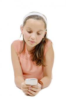 Lächelndes kleines mädchen, das auf dem boden mit telefon auf weißem hintergrund liegt