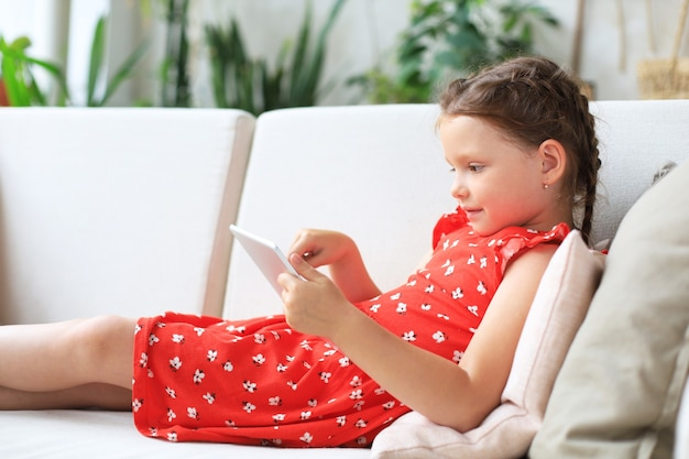 Lächelndes kleines mädchen, das auf dem sofa liegt und online-spiele spielt, informationen zum surfen im internet und lustige anwendungen auf dem tablet verwendet.