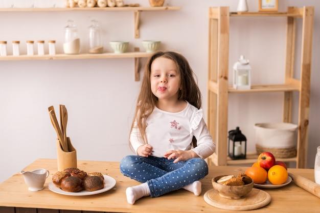 Lächelndes kleines mädchen, das auf der arbeitsfläche der küche sitzt und auf frühstück wartet. fröhliches und schelmisches mädchen in der küche.