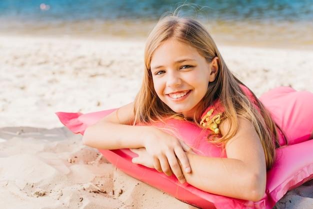 Lächelndes kleines mädchen, das auf luftmatratze auf strand im sommer sich entspannt