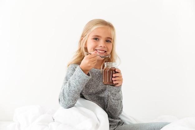 Lächelndes kleines mädchen, das bank der süßen schokoladen-haselnuss-ausbreitung hält, während im bett sitzend
