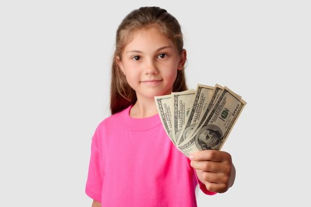 Lächelndes kleines mädchen, das eine packung geld zu einer kamera schiebt