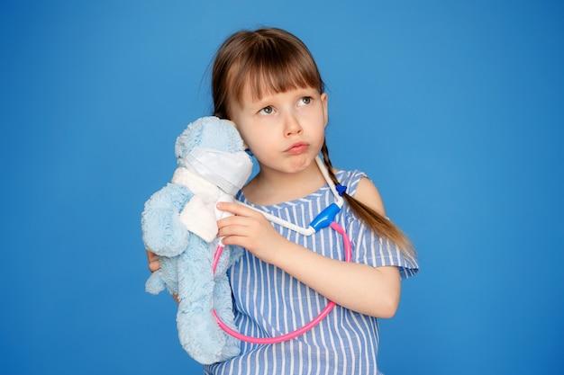 Lächelndes kleines mädchen, das einen arzt spielt und einem teddybären mit einem stethoskop lauscht, das auf einer blauen wand lokalisiert wird. tierklinikspiel. das konzept des zukünftigen berufs.