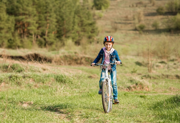 Lächelndes kleines mädchen, das fahrrad fährt