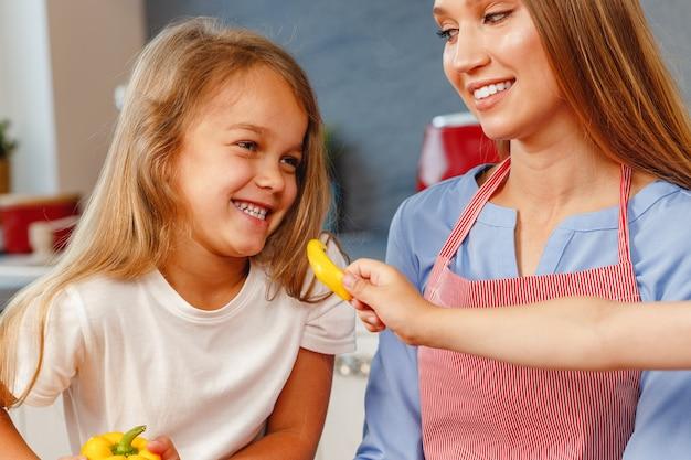 Lächelndes kleines mädchen, das ihrer mutter in der küche hilft