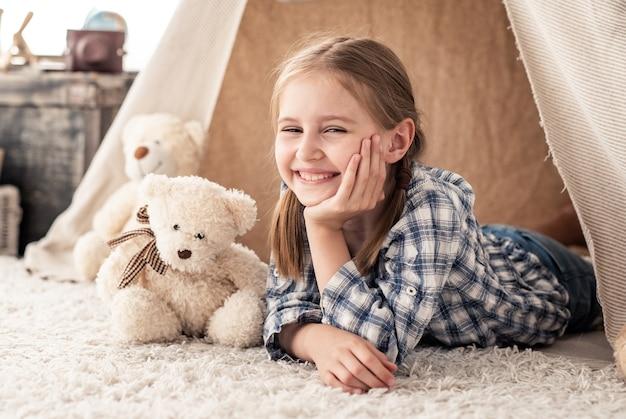 Lächelndes kleines mädchen, das im wigwam mit teddybären im kinderzimmer liegt