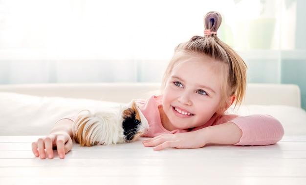 Lächelndes kleines mädchen, das meerschweinchen umarmt