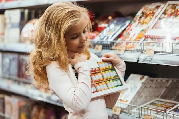 Lächelndes kleines mädchen, das süßigkeit am supermarkt wählt