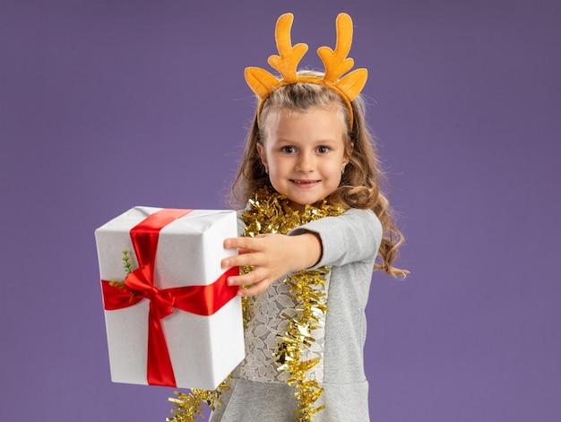 Lächelndes kleines mädchen, das weihnachtshaarreifen mit girlande am hals trägt und die geschenkbox isoliert auf blauer wand hält