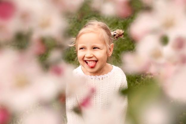 Lächelndes kleines mädchen, fotografiert durch die blühenden zweige eines baumes