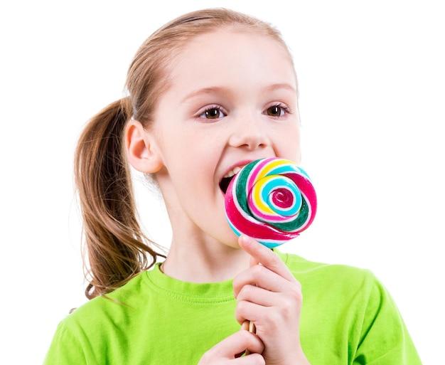 Lächelndes kleines mädchen im grünen t-shirt, das farbige süßigkeiten isst - lokalisiert auf weiß.