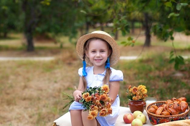 Lächelndes kleines mädchen im strohhut und mit blumenstrauß auf picknick im garten. sommerurlaub.
