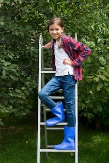 Lächelndes kleines mädchen in blauen gummistiefeln, das auf trittleiter im apfelgarten steht