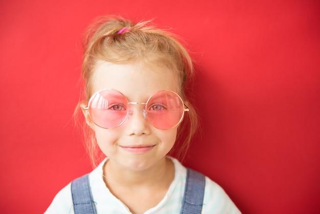 Lächelndes kleines mädchen in der großen runden rosa brille auf rotem hintergrund
