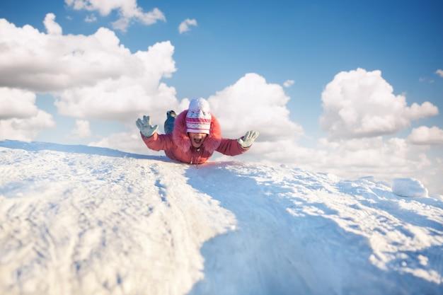 Lächelndes kleines mädchen in der winterkleidung, die bergab auf schnee reitet