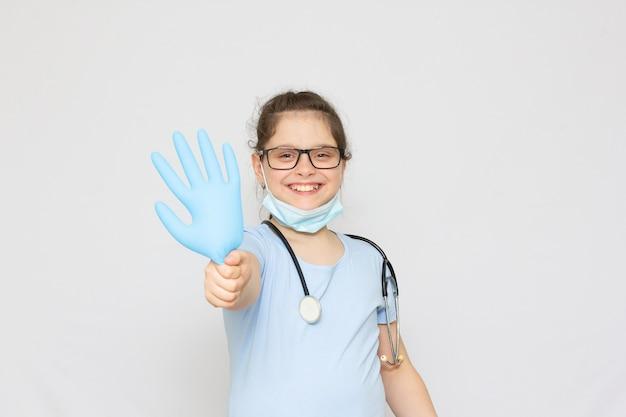 Lächelndes kleines mädchen in medizinischer uniform und blauen handschuhen, das isoliert auf weiß in die kamera schaut