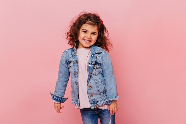 Lächelndes kleines mädchen mit dem welligen haar, das auf rosa hintergrund steht. studioaufnahme des entzückenden jugendlichen kindes, das jeansjacke trägt.