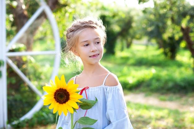 Lächelndes kleines mädchen mit einem zopf auf dem kopf hält sonnenblume im garten. kind mit sonnenblume.