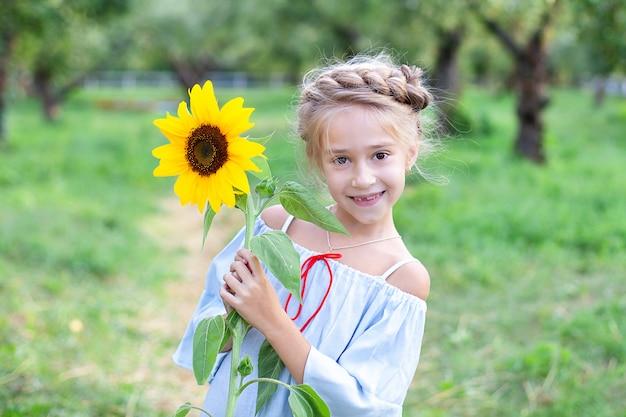 Lächelndes kleines mädchen mit einem zopf auf dem kopf hält sonnenblume im garten. kindheit. kind mit sonnenblume. kind, das natur am sonnigen sommertag genießt. nahes porträtporträt junges blondes mädchen mit sonnenblume.