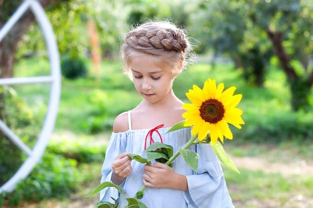 Lächelndes kleines mädchen mit einem zopf auf dem kopf hält sonnenblume im garten. nahes porträtporträt junges blondes mädchen mit sonnenblume.