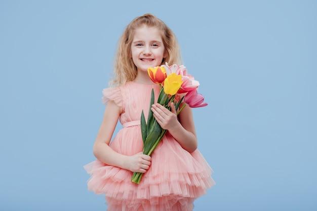 Lächelndes kleines mädchen mit frühlingsblumen-tulpen in ihrer hand, im rosa kleid, lokalisiert auf blauer wand