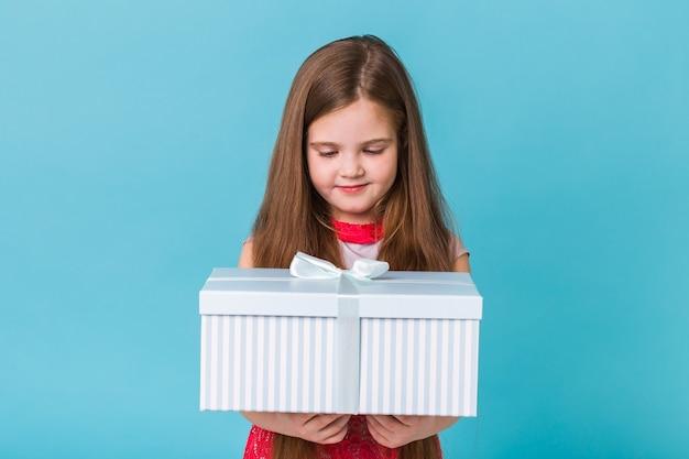Lächelndes kleines mädchen mit geschenkbox über blauer wand.