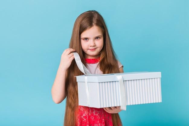 Lächelndes kleines mädchen mit geschenkbox