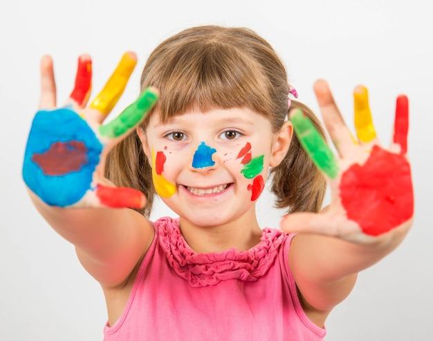 Lächelndes kleines mädchen mit in bunten farben bemalten händen