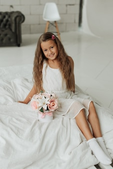 Lächelndes kleines mädchen mit langen haaren sitzt auf einem weißen bett