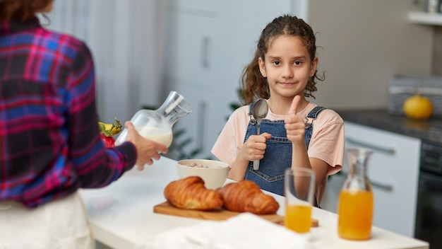 Lächelndes kleines mädchen mit lockigem haar zeigt die daumen beim gesunden frühstück zusammen mit der mutter in der küche.