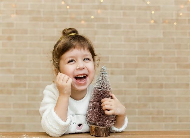 Lächelndes kleines mädchen mit weihnachtsbaum