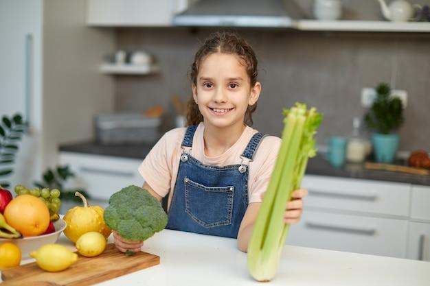 Lächelndes kleines mädchen steht in der nähe des tisches in der küche, hält grünen brokkoli und sellerie in den händen und schaut in die kamera. horizontale ansicht.